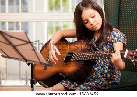 Pretty little girl practicing some new sound on a guitar at home - stock photo
