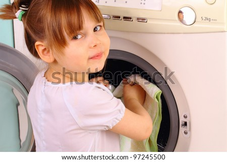 Pretty little girl puts the towels into the washing machine - stock photo