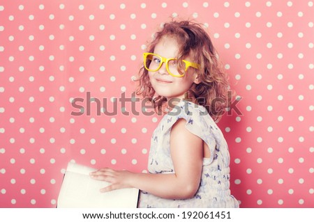 Pretty little girl reading book, smiling.  - stock photo