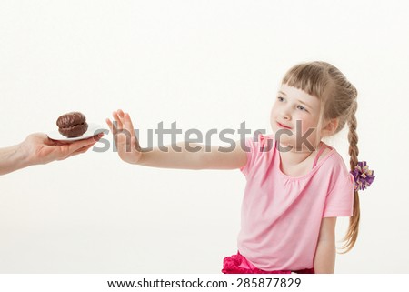 Pretty little girl rejecting a chocolate cake, white background - stock photo