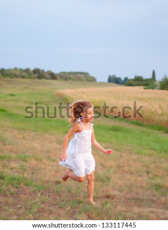 Pretty little girl running on the grass on cloudy spring day. - stock photo