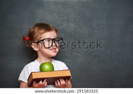 pretty little girl schoolgirl with books and apple in a school board - stock photo