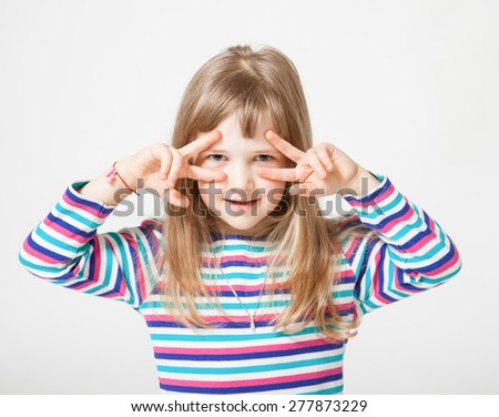 Pretty little girl showing mask from fingers on her face - stock photo