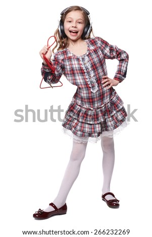 Pretty little girl singing in imaginary microphone with headphones on his head isolated over white  - stock photo