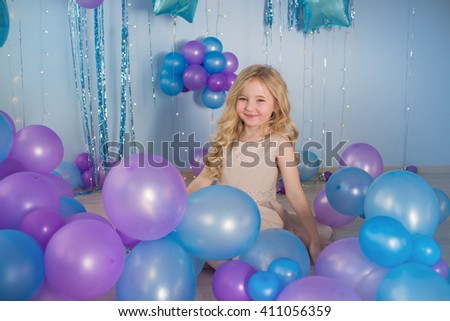 Pretty little girl sits on a floor of a studio with a lot of color balloons - stock photo
