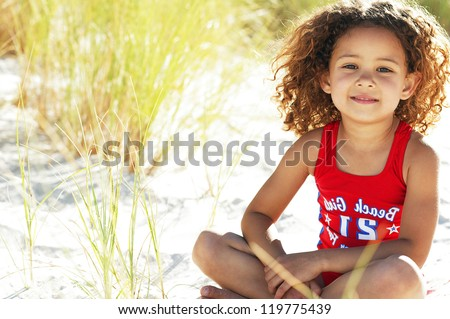Pretty little girl sitting in the sand while playing with the tall grass near the ocean - stock photo
