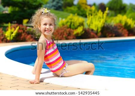 Pretty little girl sitting near swimming pool - stock photo