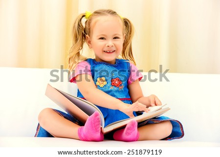 Pretty little girl sitting on a sofa and looking at a children's picture book. Happy childhood. - stock photo