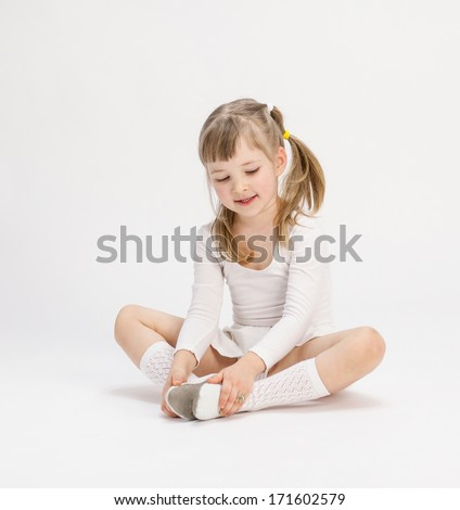 Pretty little girl sitting on the floor and doing exercise, white background - stock photo