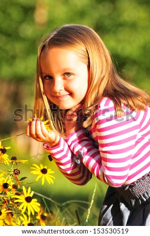 pretty little girl smelling flowers in the park on a sunny day - stock photo