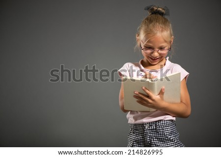 Pretty little girl smiling and posing with book. Studio shutting. Grey background.