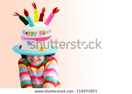 Pretty little girl smiling with a big birthday hat on her head covering half of her face - stock photo