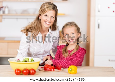 Pretty little girl standing at the kitchen counter helping her smiling attractive mother with the cooking as they cut the vegetables for a fresh salad