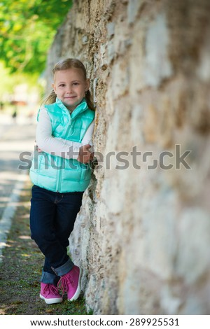 Pretty little girl standing near the wall in park - stock photo