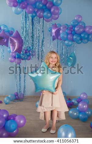 Pretty little girl stands with color balloons (star) - stock photo