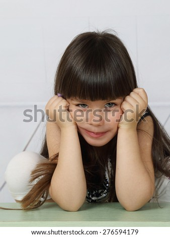 Pretty little girl supports her head by hands posed on elbows with slight dissatisfaction on her face - stock photo