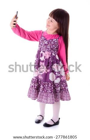 Pretty little girl taking selfie in studio - stock photo