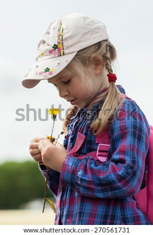 Pretty little girl tells fortunes by daisy - stock photo