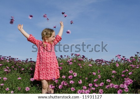pretty little girl throwing flowers - stock photo
