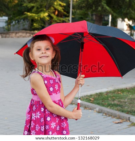 Pretty little girl walking with umbrella