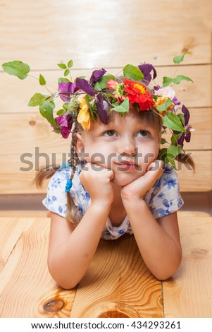 Pretty little girl wearing circlet of field flowers, dreaming about something while holding her head. Selective focus. - stock photo