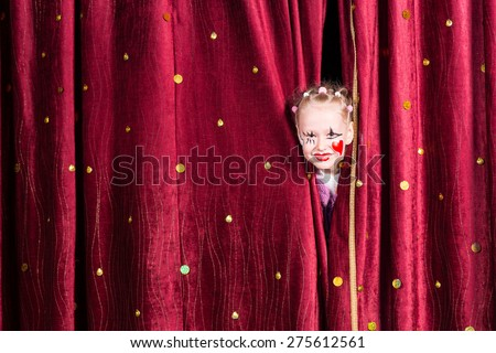 Pretty little girl wearing colorful makeup with a red heart on her cheek peering out between the curtains waiting to come out on stage during a pantomime - stock photo