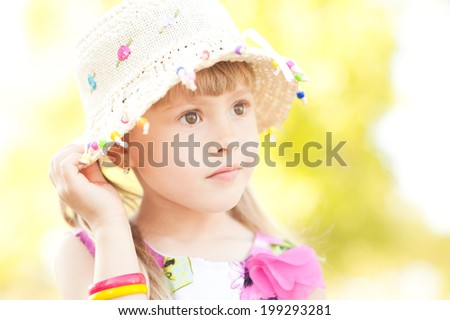 Pretty little girl wearing hat on nature background - stock photo
