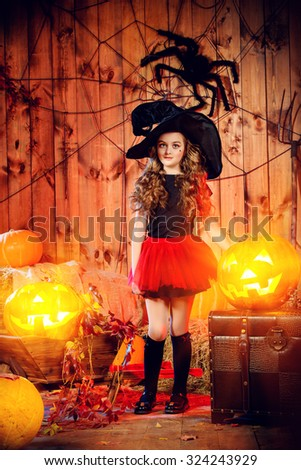 Pretty little girl witch posing with pumpkins in halloween decorations. Halloween party.