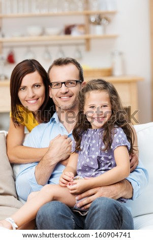 Pretty little girl with a beaming smile sitting on a sofa with her proud parents in a close embrace as they pose for a family portrait - stock photo