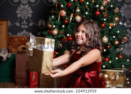 Pretty little girl with a Christmas present - stock photo