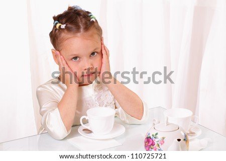 Pretty little girl with a cup and teapot - stock photo