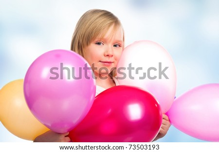 Pretty little girl with balloons over blue