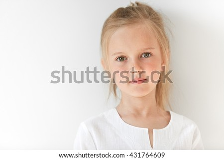 Pretty little girl with Caucasian traits looking peacfully and standing still like obedient child. She looks beautiful, attractive, nice, kind and well-mannered. - stock photo