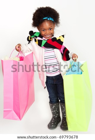 Pretty little girl with colorful shopping bags full of dresses. - stock photo