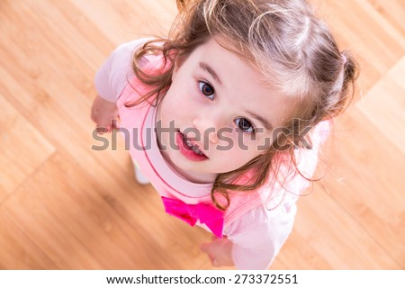 Pretty little girl with curly hair and beseeching eyes standing looking up into the camera as she asks for something that she wants, view looking down into her face with wood floor background - stock photo