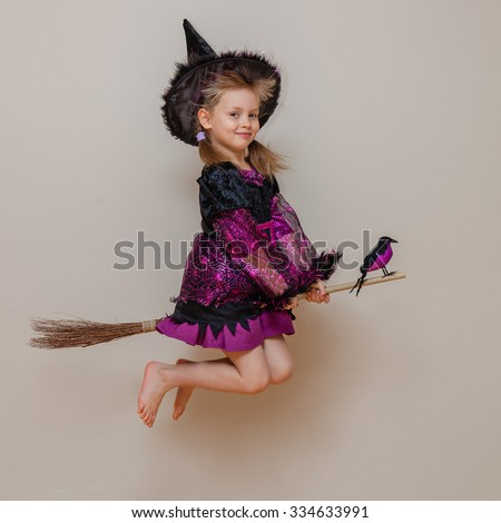 Pretty little girl with funny tricky face pretend like flying on the broom with the company of hand crow on her broom stick. Kid girl wear black and purple witch costume. Halloween coming. - stock photo