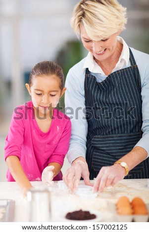 pretty little girl with grandmother baking cookies in kitchen - stock photo