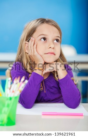 Pretty little girl with hand on chin looking away while sitting at desk in class - stock photo