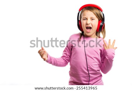 Pretty little girl with headphones singing and dancing - stock photo