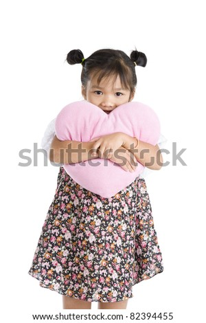 pretty little girl with heart shaped pillow, isolated on white background - stock photo
