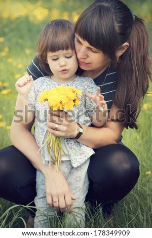 Pretty little girl with her mother holding a bouquet of dandelions