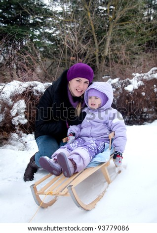 pretty little girl with her mother outdoors, winter - stock photo