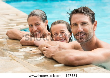 Pretty little girl with her parents in swimming pool. Happy family smiling and looking at camera in swimming pool. Portrait of a happy couple with daughter in swimming pool. - stock photo