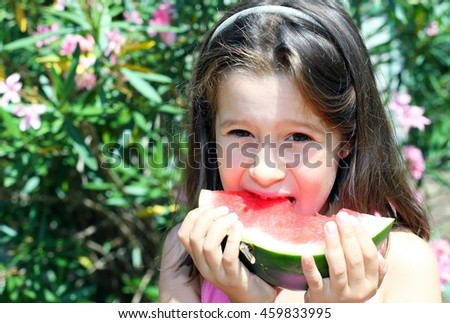 Pretty little girl with long brown hair eating a slice of ripe watermelon