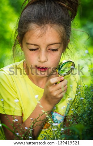 pretty little girl with magnifying glass looking at flower - stock photo
