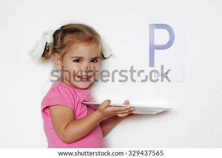 Pretty little girl with P letter smiling and holding a white plate, indoor isolated portrait over the white background - stock photo