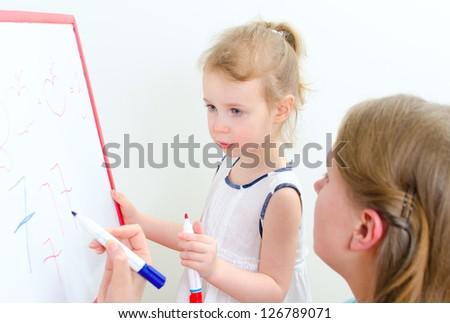 Pretty little girl with teacher near whiteboard - stock photo