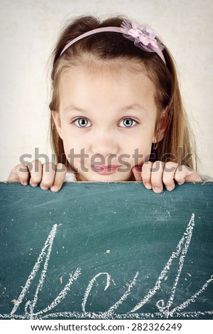 Pretty little girl writing on the  blackboard - stock photo