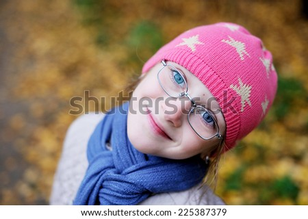 Pretty little kid  girl in glasses has fun during the walk in beauty autumn forest - stock photo