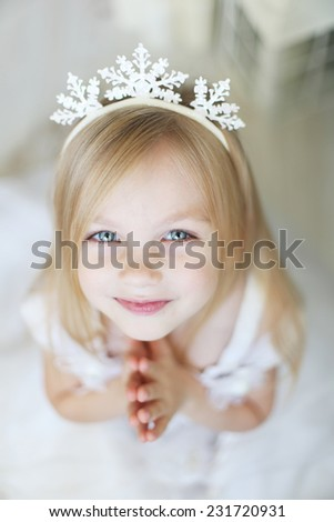 Pretty little praying girl with focus on eyes and snowflake on her head - stock photo